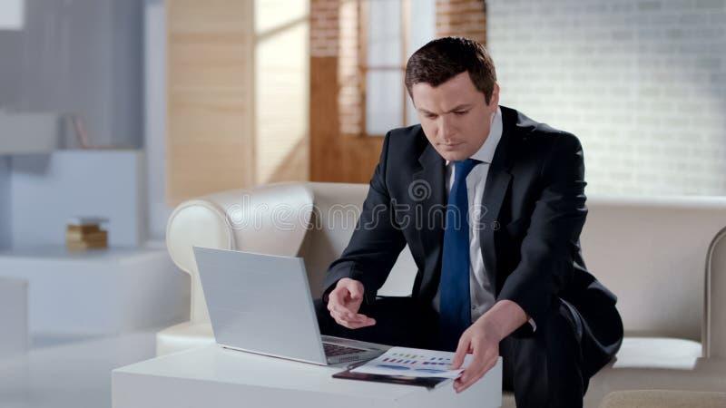 Junger Geschäftsmann, der den Finanzbericht, arbeitend an Laptop im modernen Büro überprüft lizenzfreie stockfotografie