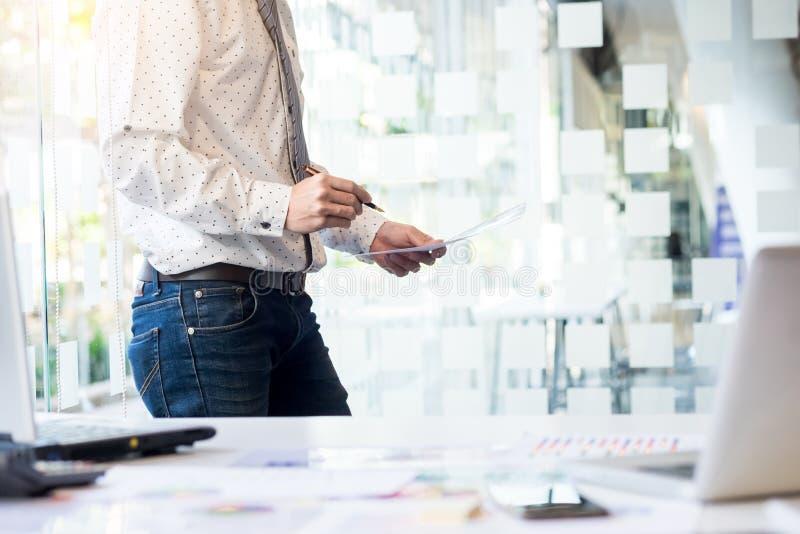 Junger Geschäftsmann, der die Dokumentenkonferenz Arbeits ist Plannin wiederholt lizenzfreies stockfoto