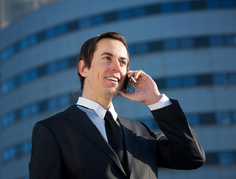 Junger Geschäftsmann, der draußen durch Handy nennt lizenzfreie stockbilder