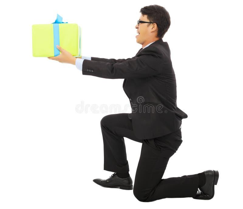 Junger Geschäftsmann, der eine Geschenkbox und ein Knien hält stockfoto