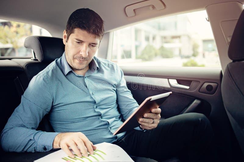 Junger Geschäftsmann, der in eine Limousine bei der Prüfung von Papieren und der Anwendung einer Tablette reist lizenzfreies stockfoto