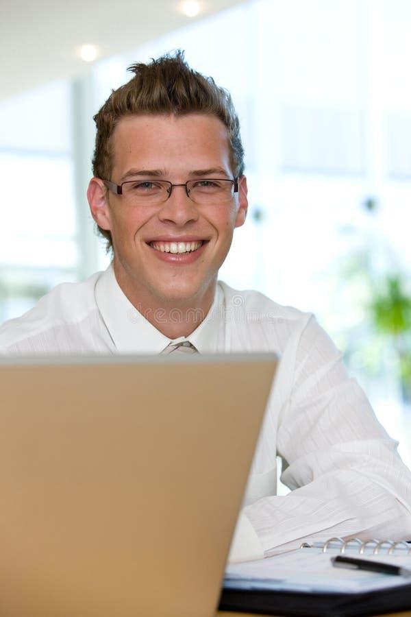 Junger Geschäftsmann, der an einem Laptop arbeitet stockbild