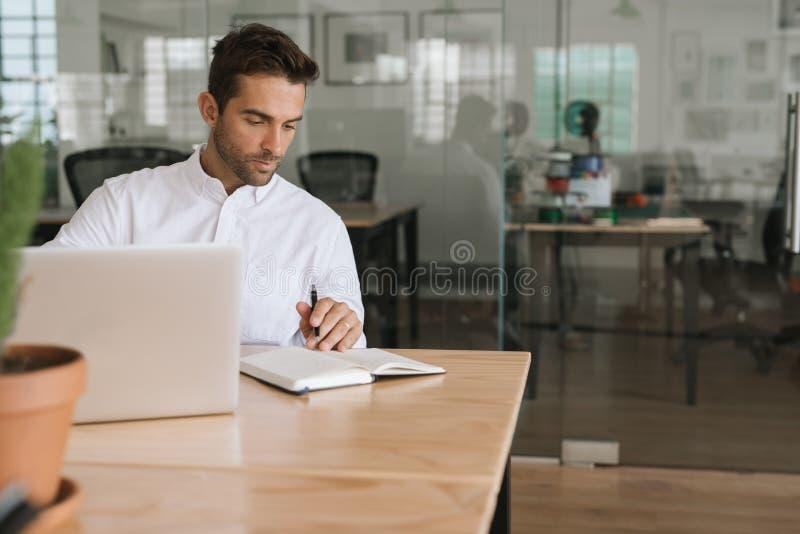 Junger Geschäftsmann, der an einem Laptop arbeitet und Anmerkungen notiert stockfoto