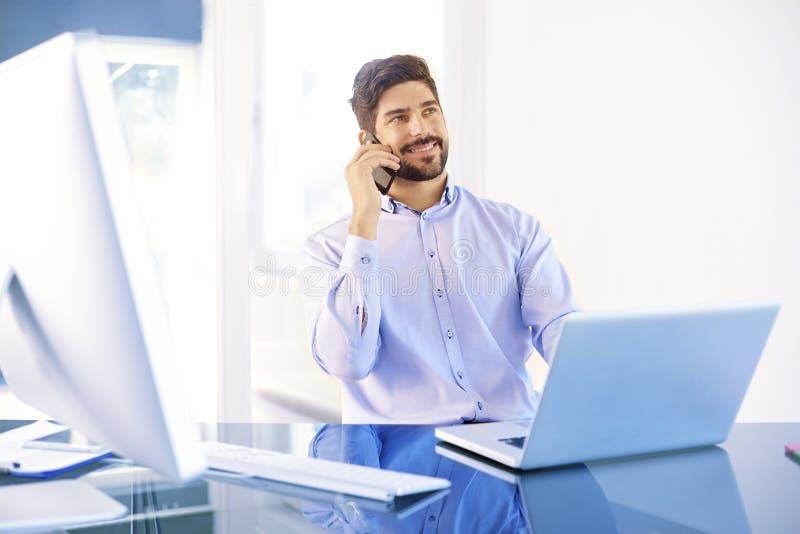Junger Geschäftsmann, der einen Anruf beim Arbeiten auf Laptop macht lizenzfreie stockfotos