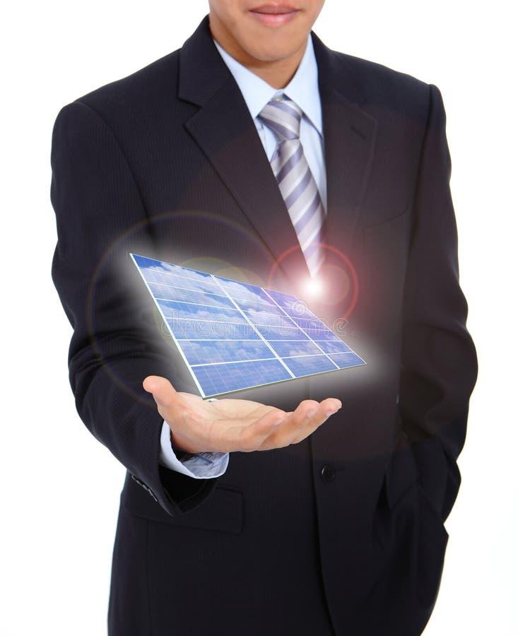 Junger Geschäftsmann, der einen Sonnenkollektor anhält lizenzfreie stockbilder