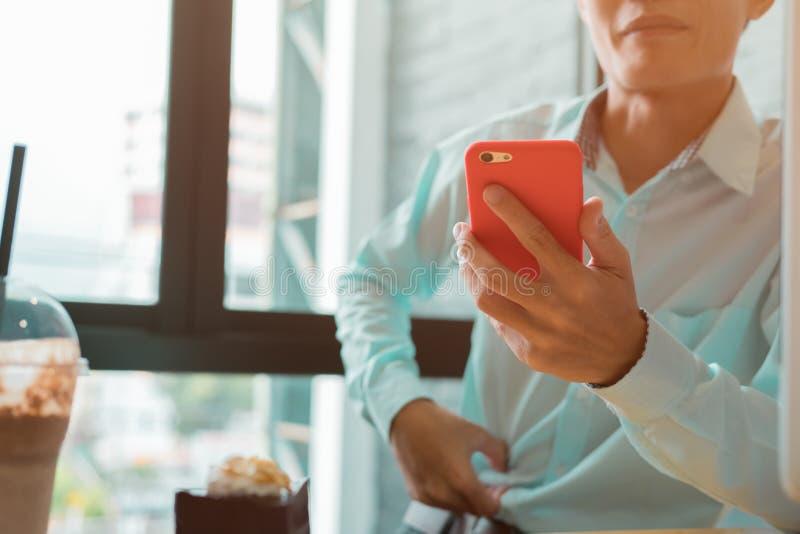 Junger Geschäftsmann, der in einer Kaffeestube überprüft sein Telefon arbeitet lizenzfreies stockbild