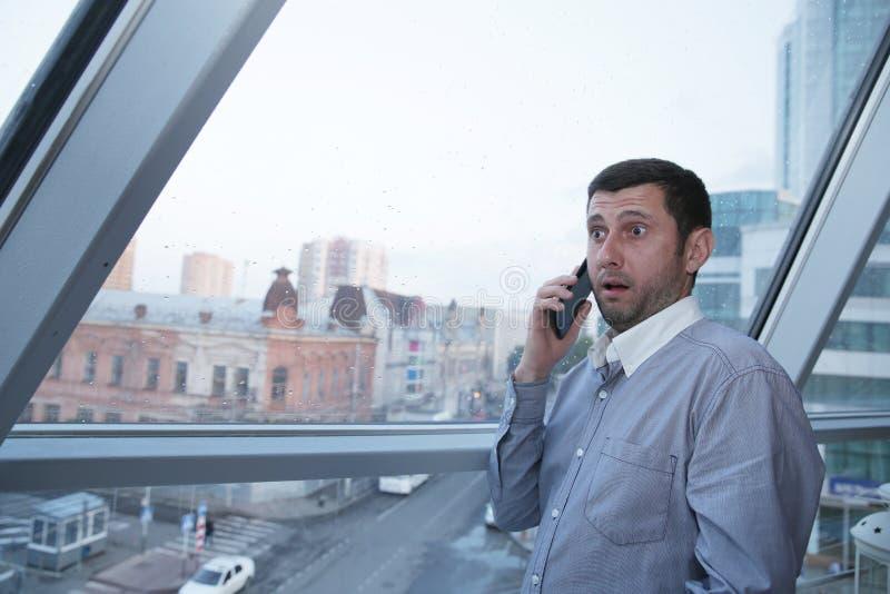 Junger Geschäftsmann, der emotional an einem Handy mit Erstaunen auf seinem Gesicht vor dem hintergrund eines panoramischen Fenst lizenzfreie stockfotografie