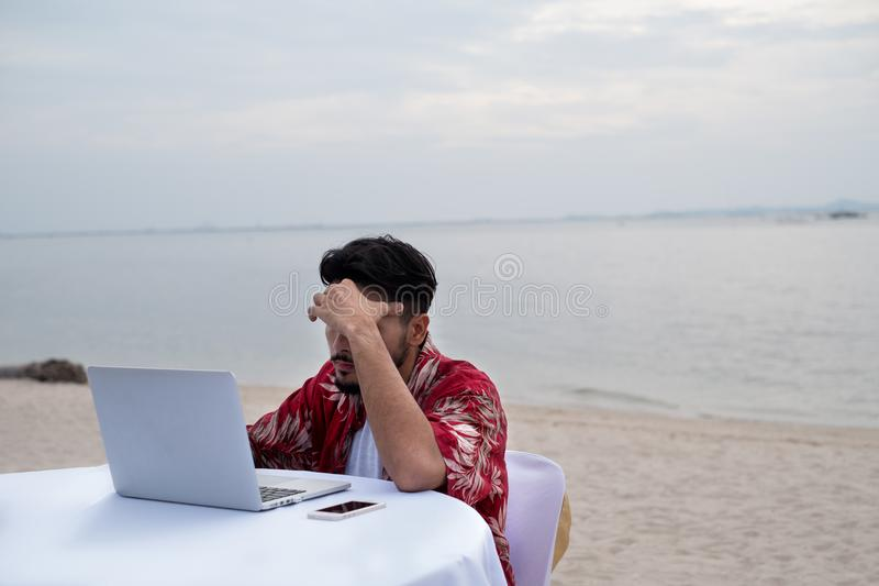 Junger Geschäftsmann, der entfernt an dem Strand arbeitet Geschäftsmann wor lizenzfreies stockfoto