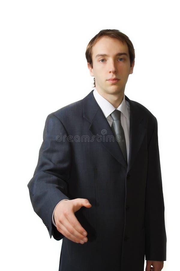 Junger Geschäftsmann, der für eine Handerschütterung sich nähert stockfotos