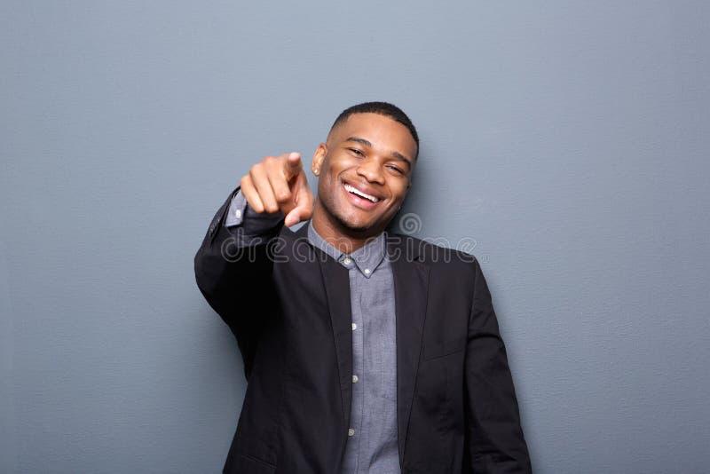 Junger Geschäftsmann, der Finger lächelt und zeigt stockbild