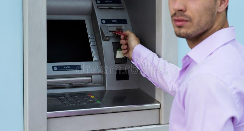 Junger Geschäftsmann, der Geld von einer Registrierkasse zurücknimmt lizenzfreie stockbilder