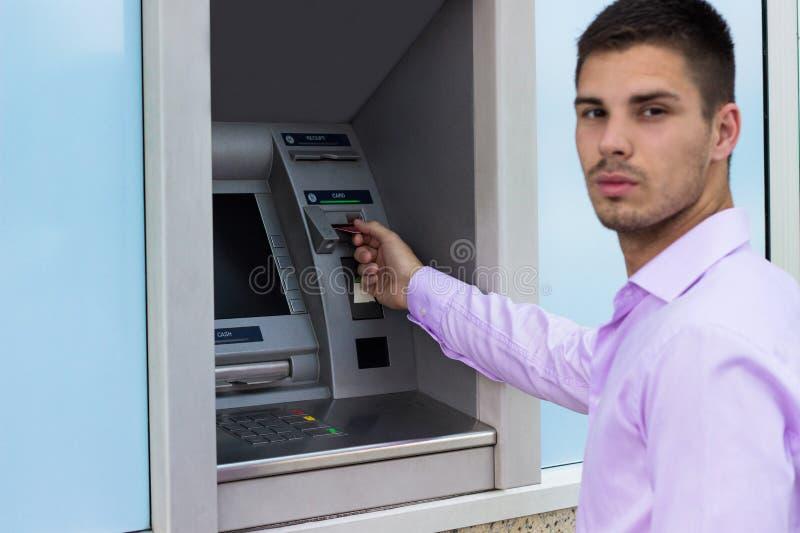 Junger Geschäftsmann, der Geld von einer Registrierkasse zurücknimmt lizenzfreie stockfotografie