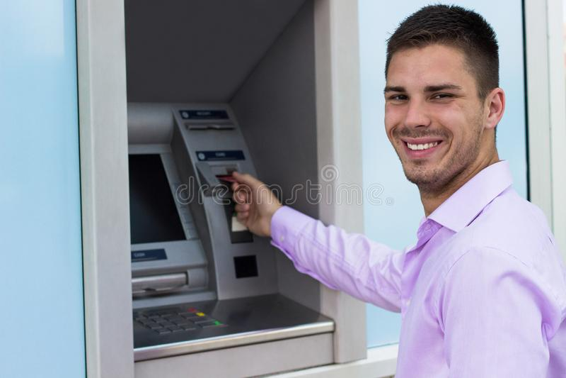 Junger Geschäftsmann, der Geld von einer Registrierkasse zurücknimmt lizenzfreies stockfoto