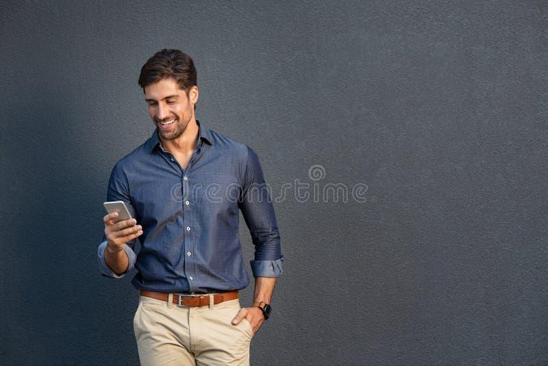 Junger Geschäftsmann, der Handy verwendet stockfotografie