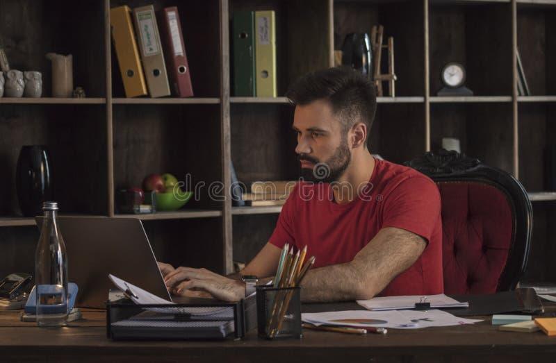 Junger Geschäftsmann, der hinter Schreibtisch mit Dokumenten sitzt und auf Laptop schreibt stockfotos