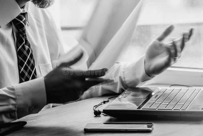 Junger Geschäftsmann, der hinter zerknittertem Papier mit dem Druck Schwarzweiss sitzt stockbilder