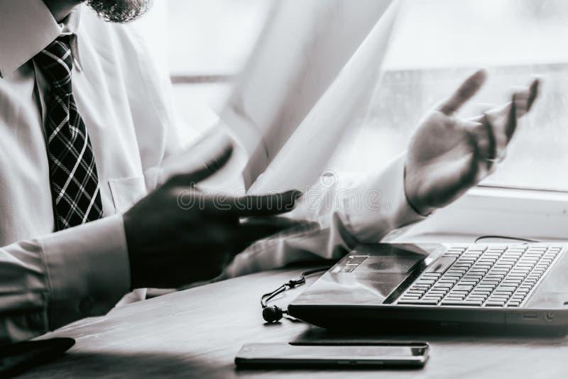 Junger Geschäftsmann, der hinter zerknittertem Papier mit den Druck Gefühl-Unschärfebeweglichen Papierdokumenten Schwarzweiss sit stockfoto