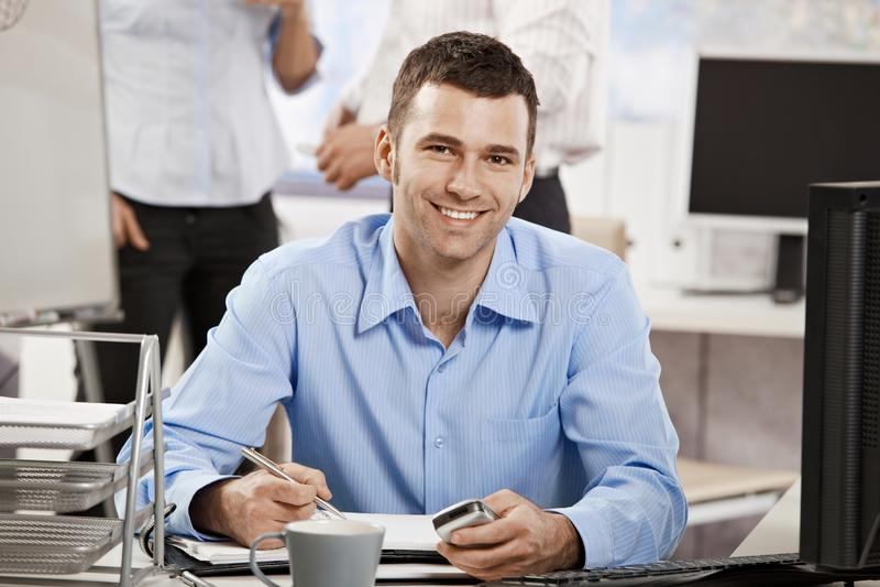 Junger Geschäftsmann, der im Büro arbeitet stockbild