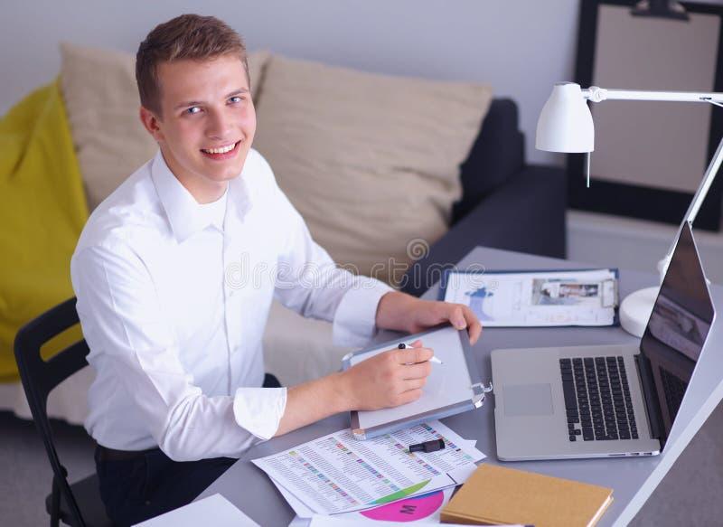 Junger Geschäftsmann, der im Büro, nahe stehend arbeitet stockfotografie