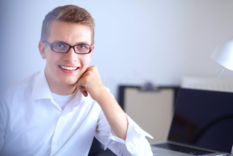 Junger Geschäftsmann, der im Büro, sitzend nahe Schreibtisch arbeitet lizenzfreie stockbilder