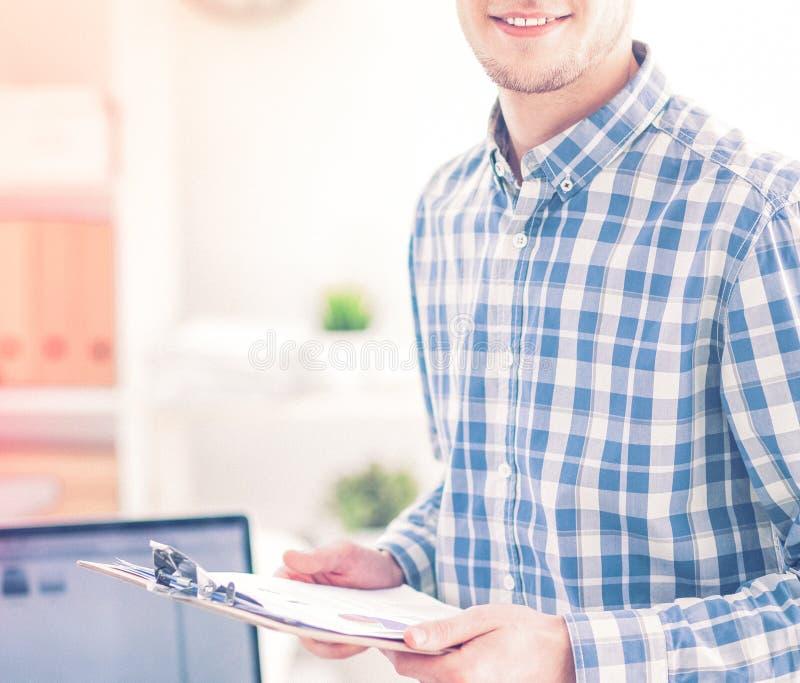 Junger Geschäftsmann, der im Büro, sitzend am Schreibtisch arbeitet stockfotografie