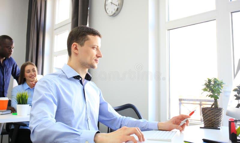 Junger Geschäftsmann, der im Büro, sitzend am Schreibtisch arbeitet stockfotos
