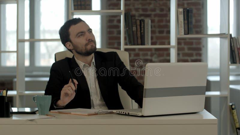 Junger Geschäftsmann, der im Büro, Suchidee sitzt stockbild