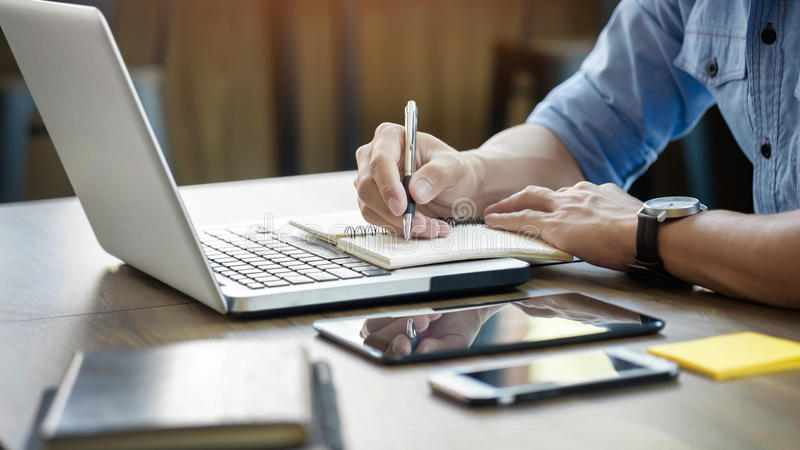 Junger Geschäftsmann, der im hellen Büro, unter Verwendung des Laptops, writi arbeitet lizenzfreie stockfotos