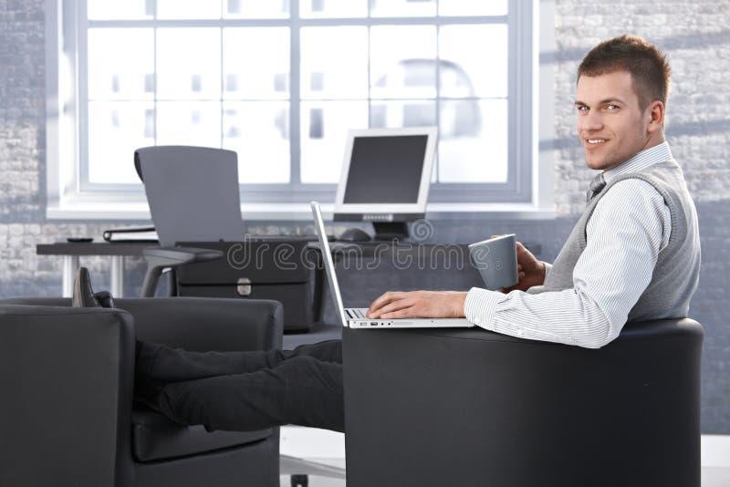 Junger Geschäftsmann, der im Lehnsessel mit Laptop stillsteht lizenzfreie stockbilder