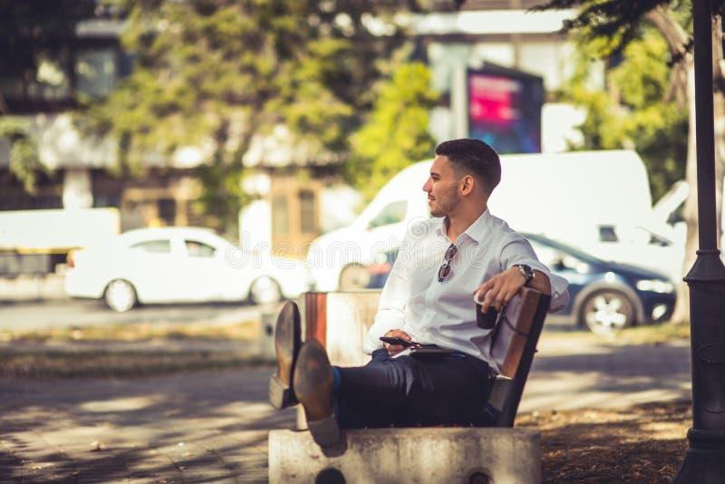 Junger Geschäftsmann, der im Park auf einer Bank liegt und stillsteht lizenzfreies stockfoto