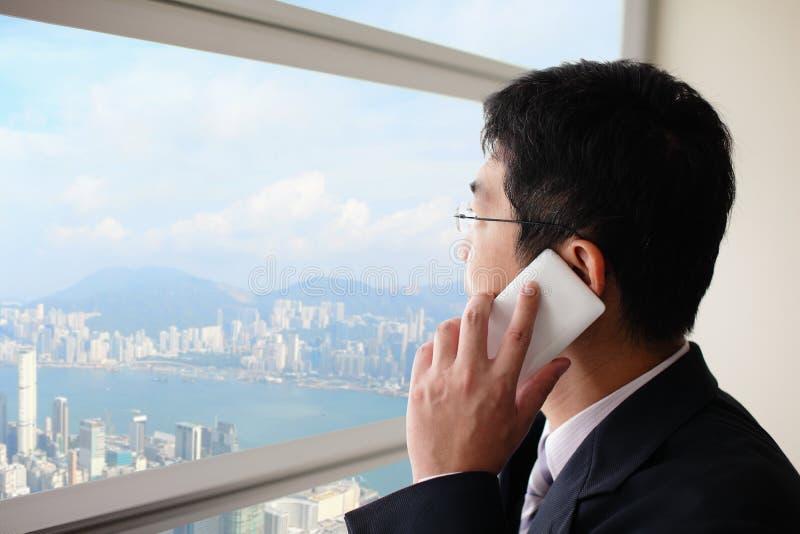 Junger Geschäftsmann, der am intelligenten Telefon spricht stockfotografie