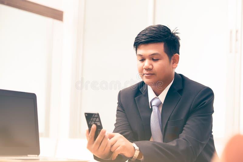 Junger Geschäftsmann, der intelligentes Telefon verwendet lizenzfreie stockbilder