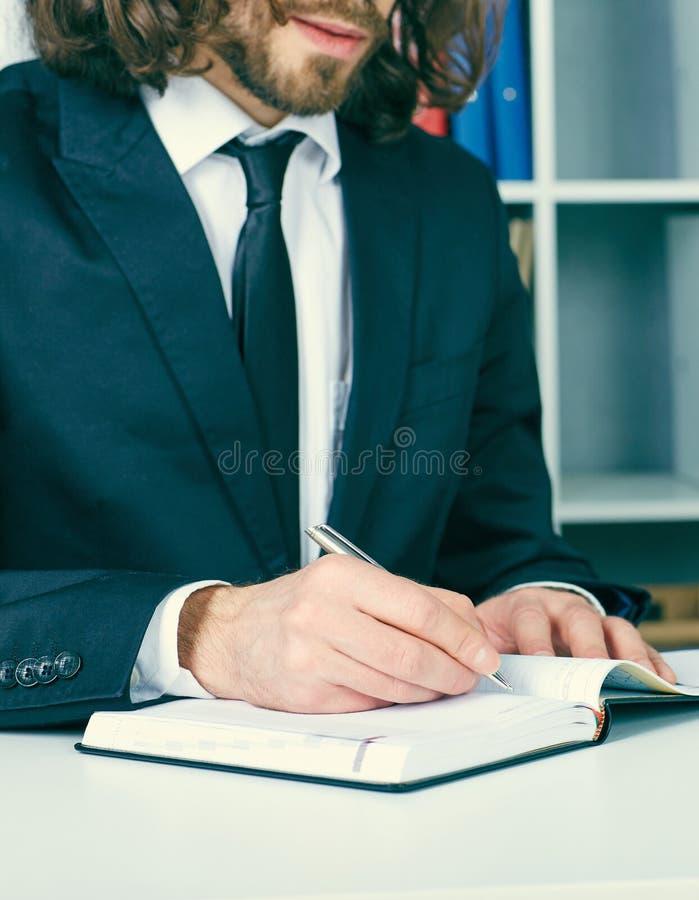 Junger Geschäftsmann in der Klage, die im Büro arbeitet, am Schreibtisch sitzt und Anmerkungen für persönlichen Organisator schre stockfotos