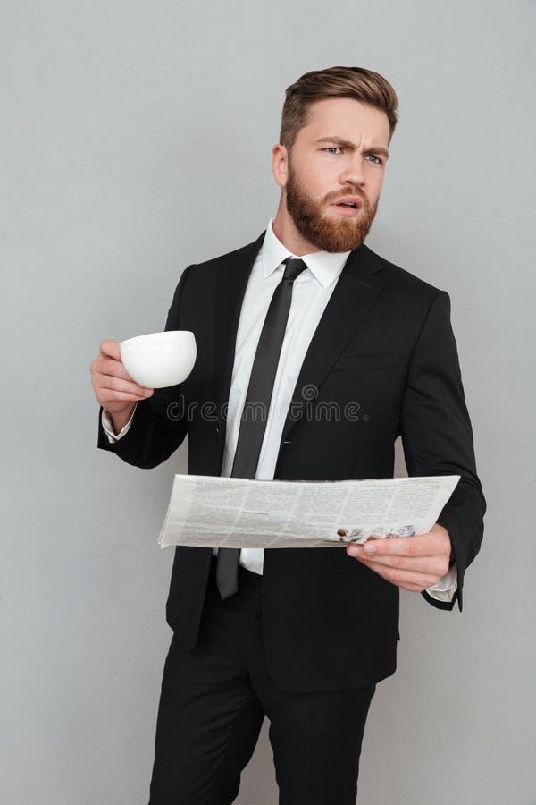 Junger Geschäftsmann in der Klage, die Zeitung und Tasse Kaffee hält stockfotografie