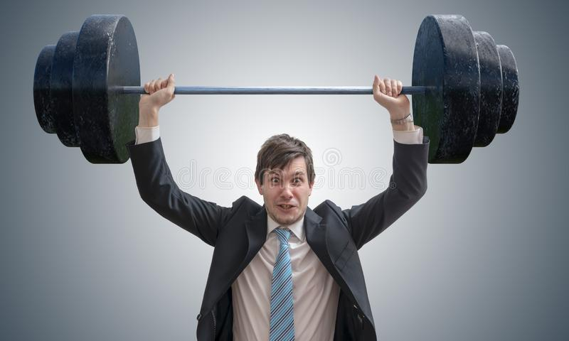 Junger Geschäftsmann in der Klage hebt schwere Gewichte an lizenzfreie stockfotos