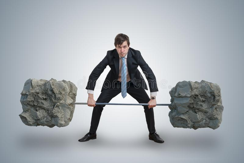 Junger Geschäftsmann in der Klage hebt schwere Gewichte an stockfotografie