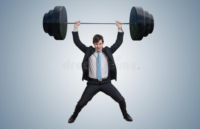 Junger Geschäftsmann in der Klage hebt schwere Gewichte an stockfotos