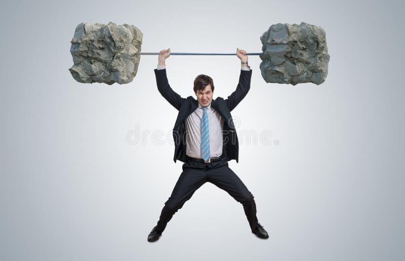 Junger Geschäftsmann in der Klage hebt schwere Gewichte an lizenzfreies stockfoto