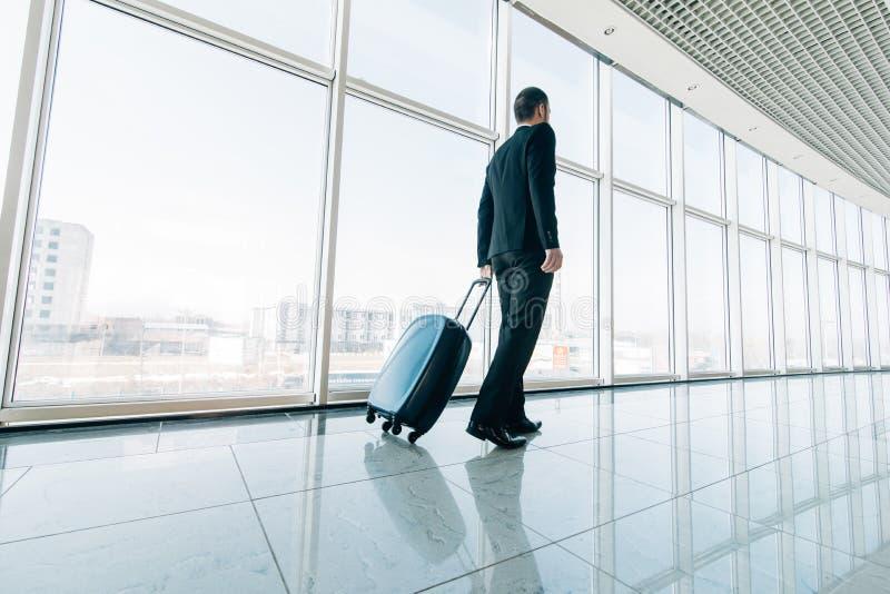 Junger Geschäftsmann, der Koffer im modernen Flughafenabfertigungsgebäude zieht Reisendes Kerl- oder Geschäftsmannkonzept Unrecog stockfoto