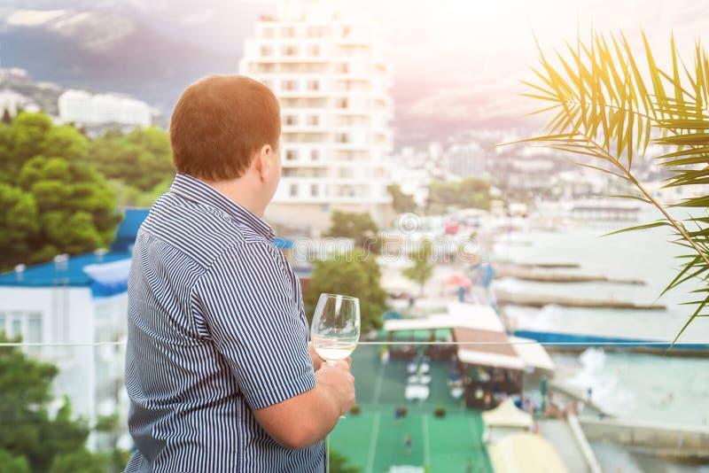 Junger Geschäftsmann in der legeren Kleidung, die auf transparentem Glasbaclony steht und auf Stadterholungsort schaut Mann, der  stockbild