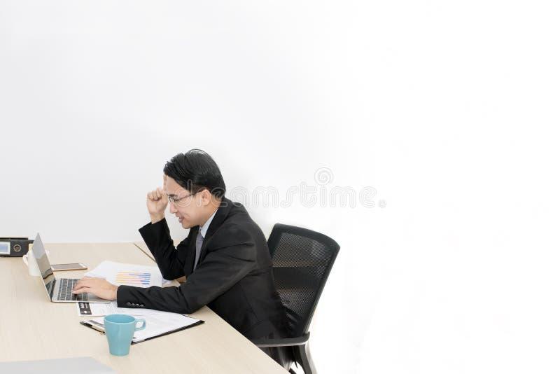 Junger Geschäftsmann, der mit Laptop und Büroartikel arbeitet stockbild