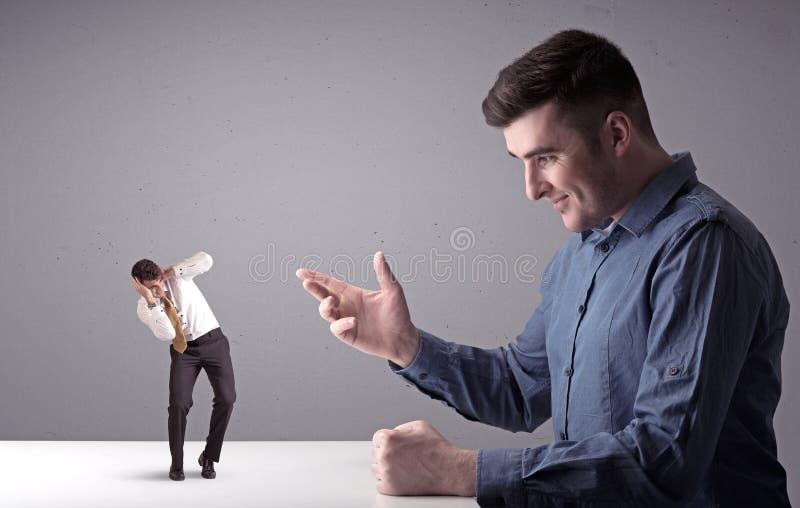 Junger Geschäftsmann, der mit Miniaturgeschäftsmann kämpft stockfotos