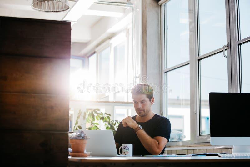 Junger Geschäftsmann, der an modernem Arbeitsplatz arbeitet lizenzfreie stockbilder