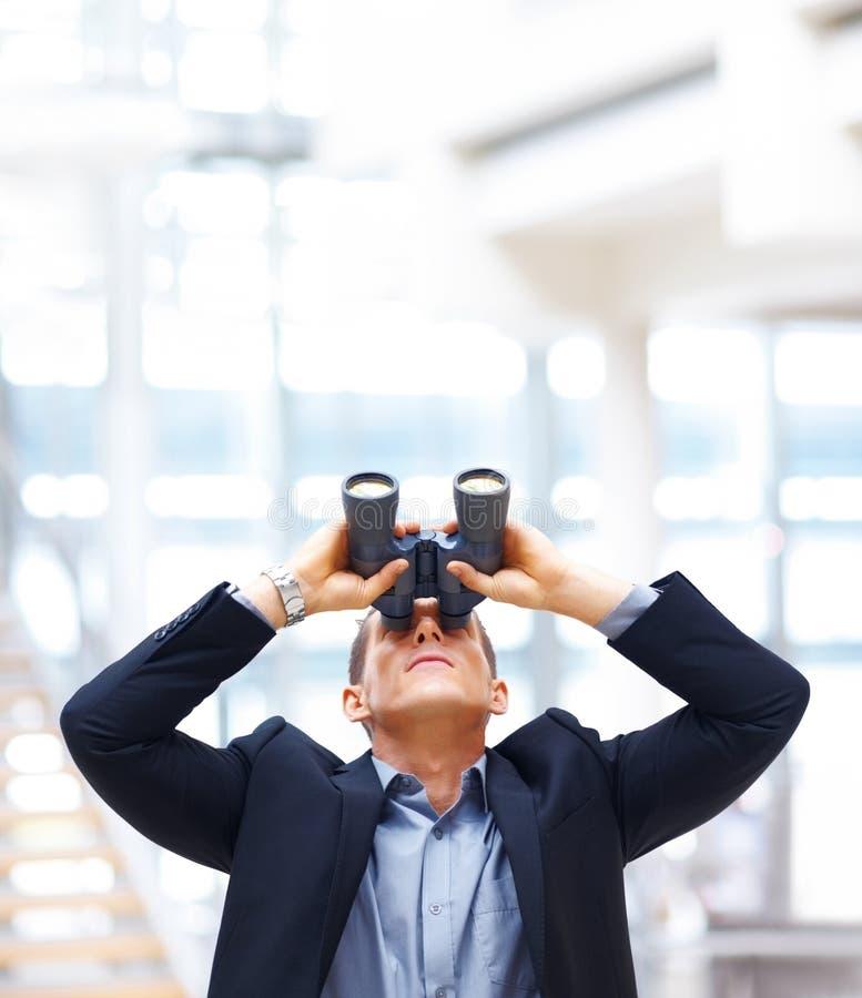 Junger Geschäftsmann, der nach Gelegenheiten sucht lizenzfreie stockfotografie