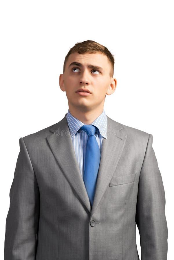 Junger Geschäftsmann, der oben denkt und schaut lizenzfreie stockbilder