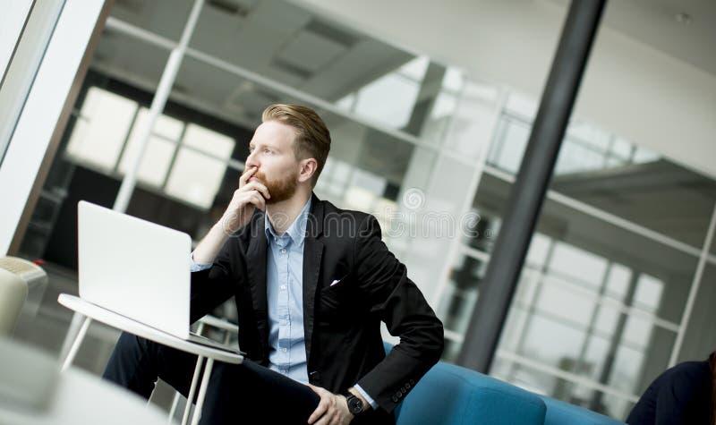 Junger Geschäftsmann der Rothaarigen, der an Laptop oder Notizbuch arbeitet lizenzfreies stockbild