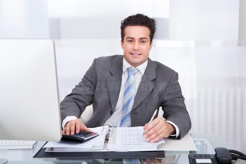 Junger Geschäftsmann, der am Schreibtisch arbeitet lizenzfreie stockfotografie
