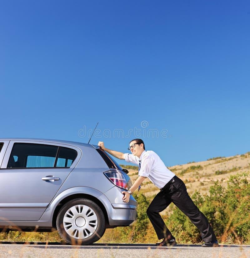 Junger Geschäftsmann, der sein Auto mit leerem Kraftstofftank drückt lizenzfreies stockbild