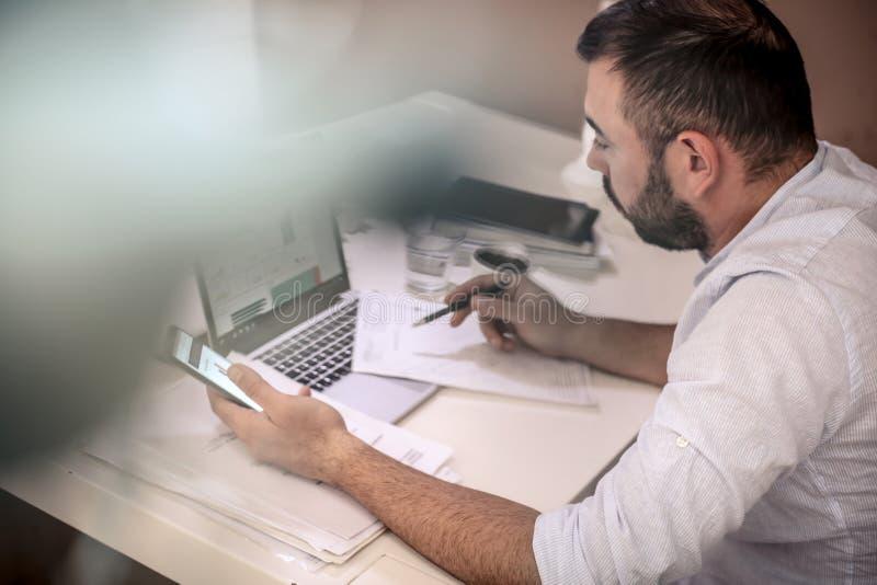 Junger Geschäftsmann, der in seinem Büro arbeitet lizenzfreie stockfotos