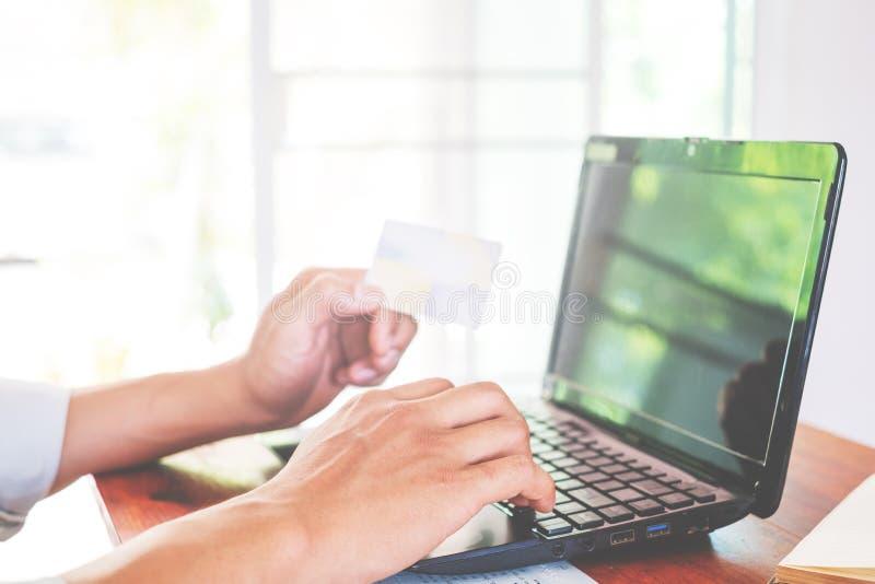junger Geschäftsmann, der an seinem Laptop arbeitet und die Kreditkarte sitzt am Holztisch in einem modernen Geschäftslokal verwe stockbild